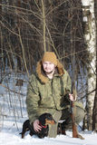 与黑达克斯猎犬和猎枪的猎人在冬天森林里 免版税图库摄影