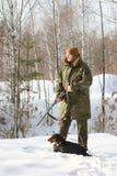 与黑达克斯猎犬和猎枪的猎人在冬天森林里 免版税库存图片