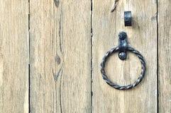 与年迈的金属门把手的老织地不很细木门以圆环的形式 免版税库存照片