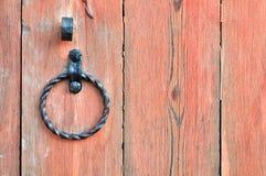 与年迈的金属门把手的老织地不很细浅红色的木门以圆环的形式 库存图片