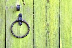 与年迈的金属门把手的老织地不很细黄色木门以圆环的形式 免版税图库摄影