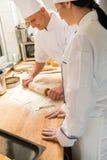 与滚针的男性厨师辗压面团 免版税图库摄影
