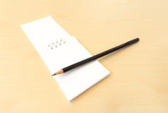与黑锋利的铅笔的白色备忘录笔记木表面上 库存照片