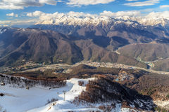 与滑雪吊车、倾斜和解决的美好的多雪的高加索山脉冬天风景在河谷 库存照片
