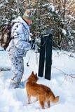 与滑雪和狗的猎人 免版税库存图片