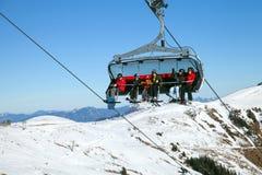 与滑雪者和snowborder的升降椅 免版税库存照片