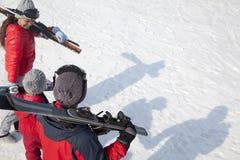 与滑雪齿轮的家庭,走在雪 图库摄影