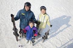 与滑雪齿轮的微笑的家庭在滑雪胜地 免版税库存照片