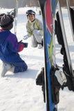 与滑雪齿轮的微笑的家庭在滑雪胜地 库存照片