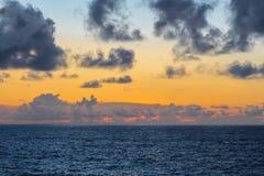 与暴风云的美好的金黄海日落 免版税库存照片