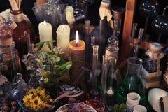 与头骨、蜡烛、烧瓶和葡萄酒瓶的神秘的静物画 免版税图库摄影