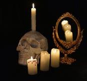 与头骨、mirrow和灼烧的蜡烛的神秘的静物画 图库摄影