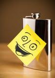 与兴高采烈的面孔的便条纸在一个熟悉内情的烧瓶sticked 库存照片