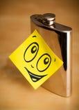 与兴高采烈的面孔的便条纸在熟悉内情的烧瓶sticked 库存照片