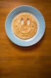 与兴高采烈的面孔的薄煎饼在板材 免版税库存照片