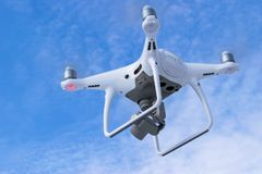 与4K摄象机的新航空器DJI幽灵4赞成quadcopter寄生虫和在天空的无线遥远的控制器飞行 通风 库存图片