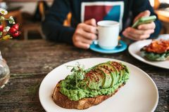 与avacado的三明治在一张木桌上 一个人给另一个人叫或写消息在背景中 库存照片