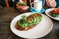 与avacado的三明治在一张木桌上 一个人给另一个人叫或写消息在背景中 免版税图库摄影