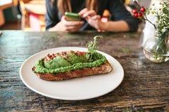 与avacado的三明治在一张木桌上 女孩给另一个人叫或写消息在 库存图片