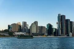 与Barangaroo点和考拉的悉尼CBD都市风景巡航有游人的小船在黄昏 免版税库存照片