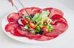 与bersaola和凉拌生菜的盘 免版税图库摄影