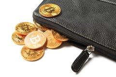 与bitcoin的标志的一些枚金黄硬币落在一个黑皮革钱包外面 库存图片