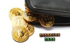 与bitcoin的标志,一部分的一个黑皮革钱包和题字`的一些枚金黄硬币接受了这里在一白色backgrou的` 免版税库存照片