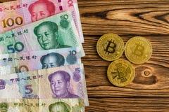 与bitcoins的被分类的汉语元在桌上 免版税库存图片