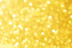 与bokeh作用的金黄闪闪发光闪烁和selectieve焦点 与明亮的金光的欢乐背景,香槟泡影 免版税库存照片