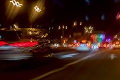 与bokeh光的都市街道夜交通 有明亮的刹车灯、城市街灯和速度的被弄脏的汽车 库存照片