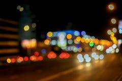 与bokeh光的都市街道夜交通 有明亮的刹车灯的,城市街灯,速度被弄脏的汽车 摘要 免版税库存图片