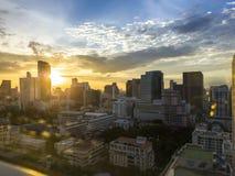 与bokeh火光的都市风景通过与温暖的阳光作用的玻璃窗对日落时间创造聚焦和阴影在bui 免版税库存图片