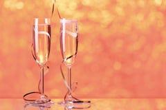 与bokeh的两块充分的香槟玻璃在背景中点燃 免版税库存图片