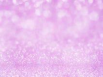 与bokeh的紫罗兰色抽象闪烁背景 点燃言情背景的模糊的软的桃红色,轻的bokeh节日晚会后面 免版税库存照片