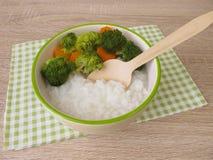 与brokkoli和红萝卜的米鞠躬 免版税库存照片