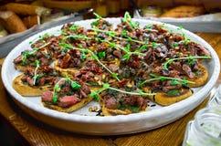 与Bruschetta、开胃菜和不同的调味汁的自助餐桌 hummus,牛肉,头脑,鲕梨,蕃茄 在一木土气tabl 免版税库存图片