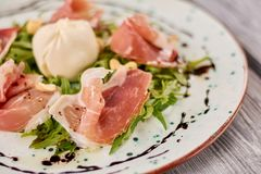 与burrata的熏火腿和芝麻菜沙拉 免版税库存图片