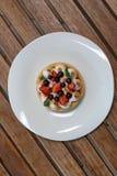 与buscuit、莓果和薄菏的小馅饼在木板条桌上的白色板材 库存图片