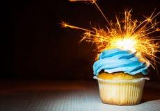 与buttercream的在木桌上的杯形蛋糕和闪烁发光物反对与拷贝空间的黑暗的背景 库存图片