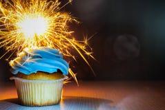 与buttercream的在木桌上的杯形蛋糕和闪烁发光物反对与拷贝空间的黑暗的背景 免版税图库摄影