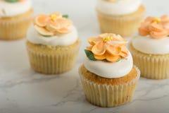 与Buttercream花的柠檬杯形蛋糕在大理石表上 库存照片