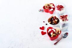与chia、格兰诺拉麦片、酸奶和莓果的浪漫早餐在老白色具体背景 概念饮食健康 免版税库存图片