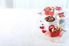 与chia、格兰诺拉麦片、酸奶和莓果的浪漫早餐在老白色具体背景 概念饮食健康 库存照片