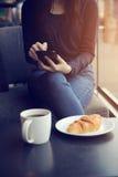 与coffe和新月形面包的亚洲女性键入的正文消息 免版税库存图片