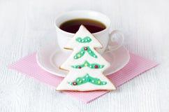 与coffe杯子的圣诞树姜饼在与桃红色餐巾的木桌上 免版税库存照片