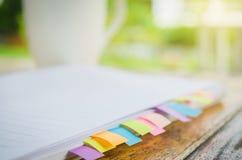 与colorfull柱子的空白的笔记本在木桌上 免版税库存照片