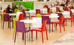 与colourul塑料椅子和桌的公开饭厅 库存图片
