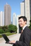 与computer 的日本商人 免版税库存图片