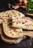 与crème fraiche、乳酪、葱和烟肉的传统Tarte flambée 免版税库存照片