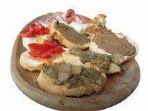 与crostini,熏火腿,肌力,在白色隔绝的一个木盘子意大利起始者的蒜味咸腊肠乳酪的典型的土气托斯坎开胃菜 免版税库存图片
